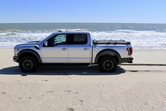 A Heavy Duty Truck Bed Cover On A Ford F150 Raptor (DiamondBack Truck Covers) Tags: aluminum tonneaucover truckbedcover diamondback diamondplate pickuptruck lightgrayorsilvertruck ford f150 raptor ruggedblack hd heavydutytruckbedcover bluesky sand beach closed noaccessories wholetruck driversideview 0015000001fxaxyaah c