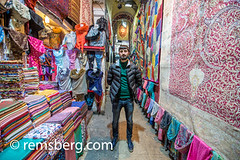 A shop owner stands with a selection of colorful scarves and tapestries at the Grand Bazaar in Istanbul, Turkey, one of the country's most visited landmarks and oldest public markets. (Remsberg Photos) Tags: istanbul turkey grandbazaar bazaar shopping commerce covered goods forsale products scarves ornate pattern detail colorful storefront store owner shop portrait tur