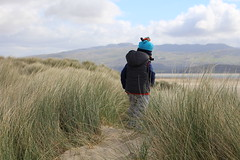 Intrepid explorer (A No NY Mouse) Tags: sand dunes wales grass boy blue hat boots horizon mountains beach sea cloud sky child cute black rock sands morfa bychan