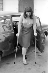 04a3871 27 (ndpa / s. lundeen, archivist) Tags: nick dewolf nickdewolf bw blackwhite photographbynickdewolf film monochrome blackandwhite april 1971 1970s 35mm austria stanton stantonamarlberg austrian people woman maggie crutches oncrutches brokenleg bandaged bandages injury car automobile gettingoutofacar legwrap legwrapped skirt necklace