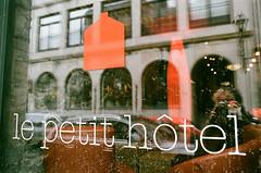 le petit hotel (Georgie_grrl) Tags: marchmontrealmission 50thbirthdaytrip withgeetha celebration party adventure montreal quebec pentaxk1000 rikenon12828mm fujifilm lepetithotel window logo reflection house me