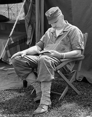 Checking out the latest paperback from the Red Cross (Jim Frazier) Tags: old costumes summer portrait people blackandwhite bw copyright heritage history totag monochrome sepia reading illinois war uniform sitting village cosplay military wwii caps hats historic september il worldwarii portraiture ww2 soldiers historical characters warriors desaturated midway costuming reenactment worldwar reenactors q3 rockford worldwar2 roles garb reenacting 2014 warfare oldified reenactments jimfrazier towm jimfraziercom adifferentpersona 20140920rockfordwwii jimfraziercom
