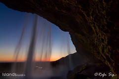Behind waterfall in the twilight