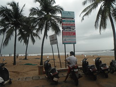 YOU CALL THIS A BEACH? (RubyGoes) Tags: red sea sky india man advertising grey sand goa bikes rules fronds bagabeach coconutpalms