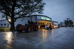 Wise Bros (Notley) Tags: water reflection puddle wet morning notley notleyhawkins 10thavenue httpwwwnotleyhawkinscom missouriphotography notleyhawkinsphotography ruralphotography architecture spring farmequipment wisebros callawaycounty callawaycountymissouri rural facade shop wisebrothers light windows tractor april 2017 rainymorning missouri wetpavement