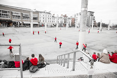 School kids in red (Dave G Kelly) Tags: cardiff outdoors people playing red schoolkids sitting wales poles selectivecolour