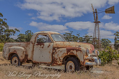 Rust in pieces 2 (Malcom Lang) Tags: fj general motors holden ute farm vehicle car automobile auto rusty crusty rust wheels tyres windmill fence vines grapes headlights bumper bar tray nuts windows doors glass old trees sky grass wornout post clouds canoneos6d canon canonef2470mm canon6d canonef mal lang photography