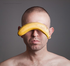 man with his identity hidden behind a banana (Ramn Espelt) Tags: man color ecology face yellow fruit idea funny natural skin symbol head expression background young vegetable banana hidden identity human faceless concept agriculture anonymous facial isolated unidentified anonymity sustainabledevelopment unrecognizable
