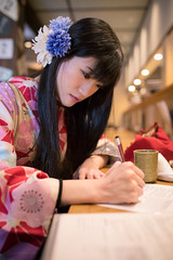 Young woman in Kimono writing document in restaurant (Apricot Cafe) Tags: img26188 2024years asia asianandindianethnicities higashichayamachi ishikawaprefecture japan japaneseethnicity japaneseculture kanazawa kimono sigma35mmf14dghsmart architecture charming cheerful citylife day enjoyment fashion freedom freshness hairaccessory happiness indoors lifestyles longhair lunch oldfashioned oneperson onlywomen pen photography relaxation restaurant sitting smiling springtime tourism traditionalclothing tranquility travel traveldestinations vertical walking weekendactivities women writing youngadult kanazawashi ishikawaken jp