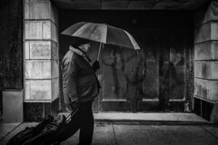 A traveling man (R*Wozniak) Tags: blackwhite bw blackandwhite milwaukee monochrome streetportrait street city rain umbrella nikon nikond750 35mm