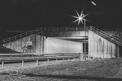 Streetlight underbridge (Iain Jaques) Tags: bw mono longexposure nighttime night sodium streetlight bridge underbridge concrete concretebridge a453 crashbarrier lensflare roadsign