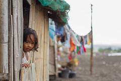 Girl Peeking From Window (AdamCohn) Tags: beach window girl blacksand coast philippines laundry peek clothesline filipina pinoy legazpi adamcohn wwwadamcohncom