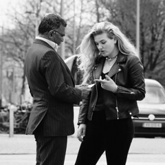 Discussion about a Note (d_t_vos) Tags: discussion man woman note youngwoman teen teenager street streetphotography streetportrait streetview trees outside candid people car railwaystation parkingplace suit jacket blond blonde leather hand hands fingers squared amsterdam zuid gustav mahlerplein monochrome zwartwit contrast conversation quarrel dickvos dtvos