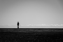Walking alone (dharder9475) Tags: 2016 alone bw blackandwhite expansive grass highcontrast man montroseharbor privpublic sky solitary wide