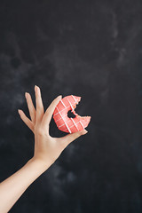 Pink donut in a woman's hand on black background (SiberianImages) Tags: background bakery black cafe cake delicious dessert food france french blue sweet almond hand handyman home macaroons menu products shop close up closeup assortment bake biscuit blueberry brulee candy coconut coffee color colorful confection cream creme female flavor gourmet green lemon macro orange pastry pistachio put donut pink red bite