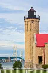 Lighthouse and the Mighty Mac (Kenneth Keifer) Tags: road old bridge light usa lighthouse lake brick tower clouds point construction mac highway long crossing suspension steel famous engineering landmark historic greatlakes upper maritime transportation tall nautical lower marvel juxtaposition straits beacon huron creamcitybrick mackinac roadway mackinaw peninsulas interstate75 mackinawcity mightmac