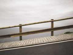 Slope with a wooden railing (Ramn Espelt) Tags: road wood sea sky detail composition outdoors wooden day cloudy background horizon gray overcast nobody downhill sidewalk concept railing asphalt uphillslope