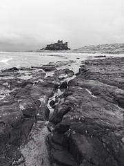 Bamburgh Castle (Robin Mulligan) Tags: sea water stone rock blackandwhite scenic castle beach landscape iphoneography iphone bamburghcastle 100v10f 500v20f