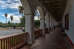 There were voices down the corridor (tquist24) Tags: california hbm hdr nikon nikond5300 oldsantabarbaramission santabarbara architecture bench clouds fence geotagged palmtree palmtrees sky tree trees vacation arch arches corridor tile tiles