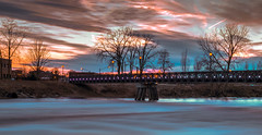 Hurry up and wait... (tquist24) Tags: hdr indiana mishawaka nikon nikond5300 outdoor stjosephriver bridge clouds evening footbridge geotagged lights longexposure reflection reflections river sky sunset tree trees water unitedstates