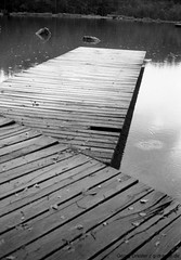 Planks (ge-org) Tags: wood lake water rain analog blackwhite walkway rollei35 ilfordhp5plus chiemgau zellersee ilfordhp5400 film:iso=400 film:brand=ilford sprsinn film:name=ilfordhp5400 filmdev:recipe=9658 spuersinnhcd803generation