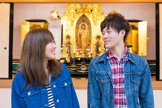 Young couple talking in front of Buddha altar