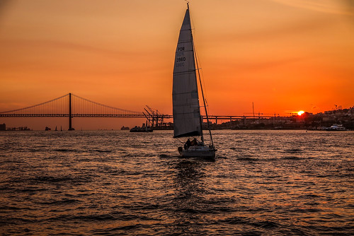 sailing around Lisbon, Portugal, between  Torre de Belem to Panteao Nacional - sunset paints the Ponte 25 de Abril and other boats with colour.