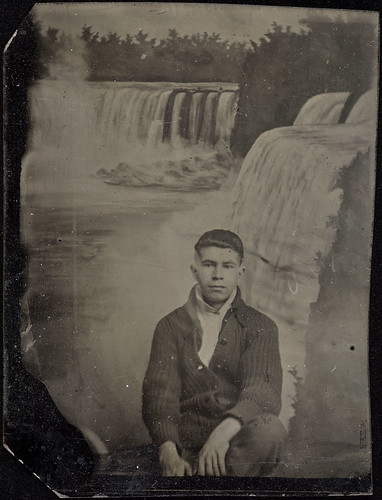 Portrait of a young man sitting in front of a Niagara Falls backdrop / Jeune homme assis devant un décor représentant les chutes Niagara