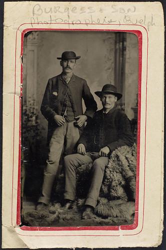Portrait of two men, one standing and one sitting, both wearing hats, Guelph, Ontario / Deux hommes, un debout et un assis, coiffés de chapeaux, Guelph (Ontario)