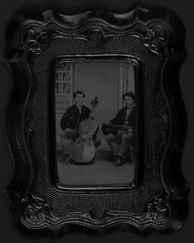 Portrait of two men, one holding a violin and the other holding a cello / Deux hommes, l'un tenant un violon et l'autre un violoncelle