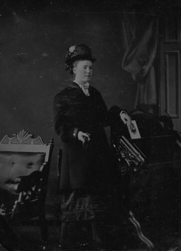 Portrait of a woman standing next to a desk and holding a photograph, Shelburne, Ontario / Femme se tenant près d'un bureau, une photographie à la main, Shelburne (Ontario)