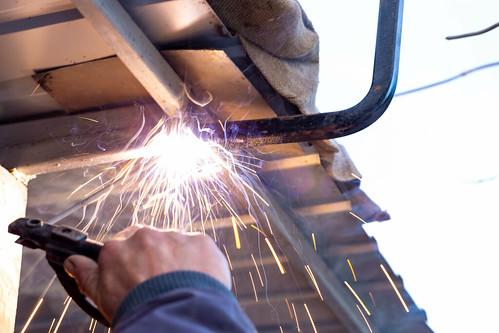 Man welder working welding with electrode outdoors