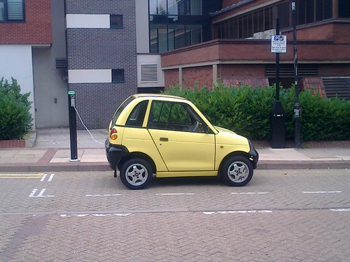 G-Whizz - Electric yellow car charging on Aston Street