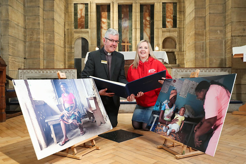 Christian Aid Week launch at Belfast Cathedral: Rosamund Bennett (Christian Aid) and Dean Stephen Forde with the book of remembrance and photos of Jebbeh and Tenneh.