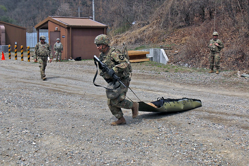 U.S. soldiers drag a simulated casualty on a stretcher during 2019 2nd ID Best Warrior Competition