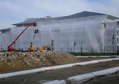 BTP Renovation Urbaine Demolition - Protection d'un bâtiment voisin par une membrane géotextile