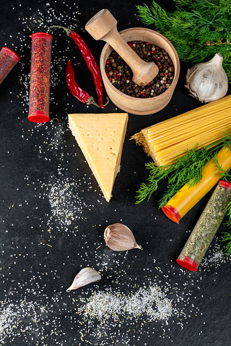 Raw spaghetti with cheese and spices on a black background