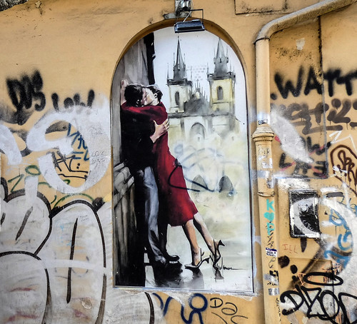 A kissing couple between other graffiti on a wall under the Charles Bridge in Prague