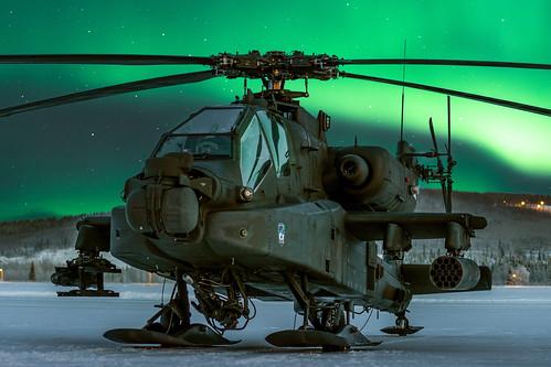 An AH-64D Apache rests under an aurora sky