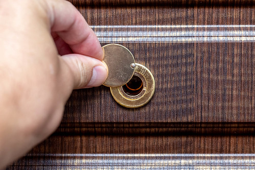 A man's hand opens the peephole on the door