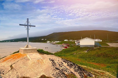 LOST AT SEA. A cross, honoring those taken by the sea, sits on top of a hill looking down at the village in St. Lewis, Labrador. #travel #explorenewfoundland #visitnewfounlandandlabrador . . . . . #instapassport #aroundtheworldpix #ig_masterpiece #campina