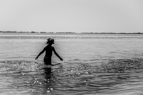 Elle avançait lentement, ses mains caressant l'eau. Le soleil, brillant de mille feux, se baignait avec elle. Canicule, été 2019.