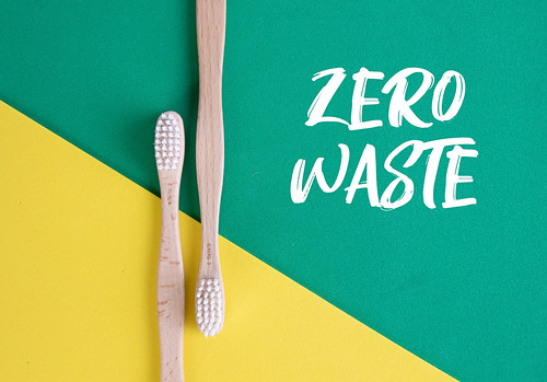 Wooden toothbrushes with Zero Waste text on green and yellow background