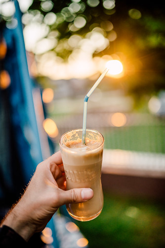 A young man holding a glass of iced coffee at home at sundown. Happy hour non-alcoholic beverage