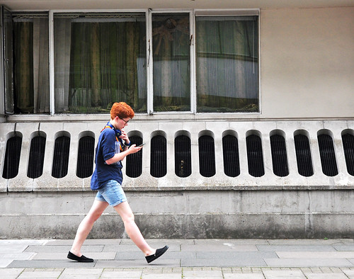 Man wearing shorts with smart phone walking by window and holes in wall
