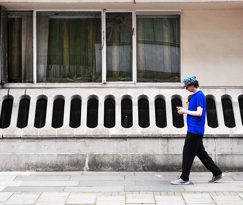 Man in blue shirt with smart phone walking by window and holes in wall