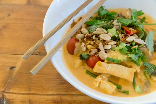 Nahaufnahme von veganem, vietnamesischem Essen: Fleischloses Bio-Tofu-Curry mit Nüssen, Kräutern und Essstäbchen, auf einem Holztisch