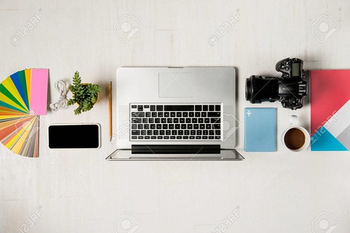 Work space for photographer, graphic designer. Flat lay of laptop, camera, colorchart, digital tablet, coffee cup, book, pencil on wooden table.