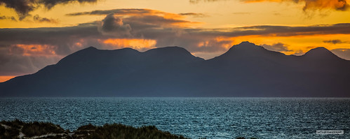 Telephoto image of the Island of Rum under a fiery sunset from the sand-dunes of the glorious Camusdarach Beach.