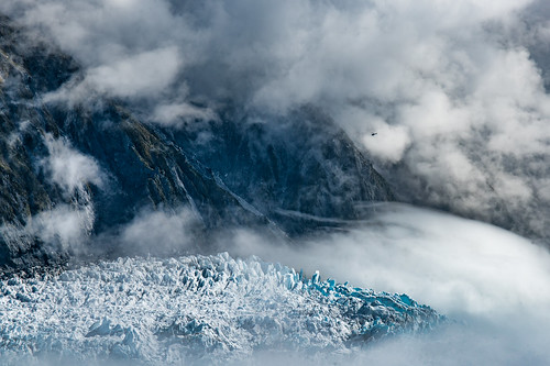 Spot the tiny  helicopter flying over the NewZealand Southern Alps glacier between the cloud layers